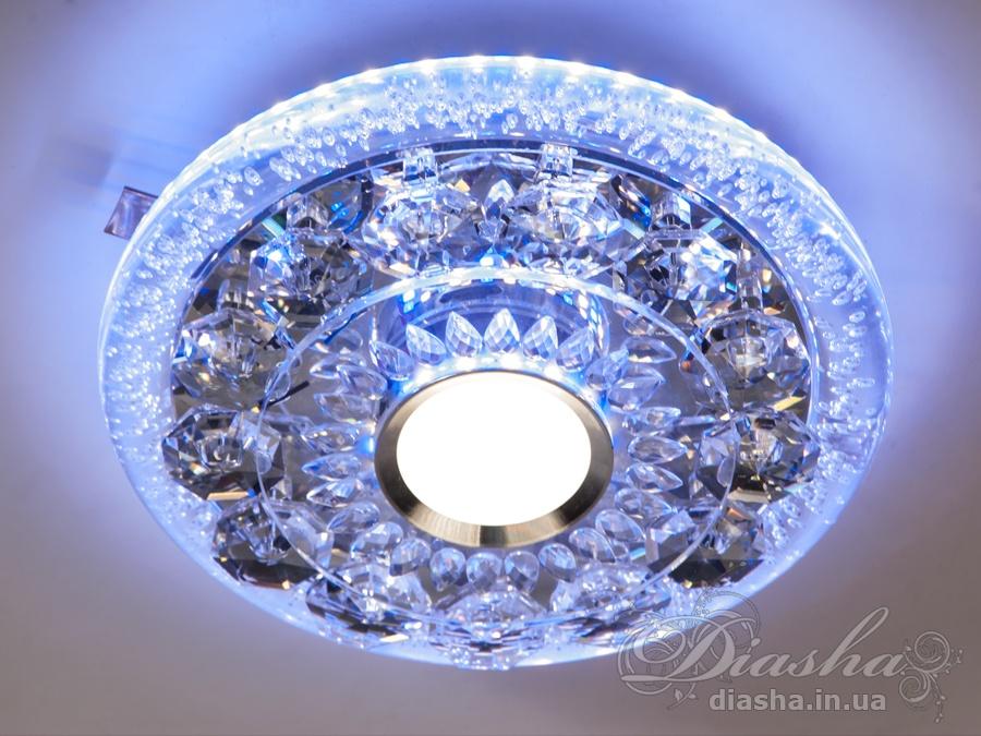 Светильник оснащен встроенным LED модулем 28W. С возможностью выбора цвета свечения. Светодиодный свет преломляется в сотнях граней точечного светильника и равномерно распределяется по помещению. Светильник экономичен, красив, современен и изготовлен из качественного хрусталя, что обеспечивает ему хорошее преломление света и образование четких ярких бликов. Теперь наши светильники способны создать приятное освещение даже для тихих семейных посиделок. Светильник управляется от обычного одинарного выключателя, и может работать в трёх режимах: спокойный нейтральный свет, яркая торжественная подсветка, максимально подчёркивающая хрусталь, режим минимального яркости - свет нейтрального спектра идёт только вниз, а по комнате пузырьками воздуха в окружающем светильник стекле рассеивается приятная синяя подсветка. Светильники этой модели могут быть установлены в отверстие 100мм, или как накладные светильники. Весь необходимый крепеж в комплекте. Точечные светильники просты и легки в установке, поэтому их монтаж не займет много времени и труда. Они запросто могут изменить пространство помещения. Если точечные светильники установить по периметру потолка, то он будет казаться выше, а сама комната – намного больше. Примите это как руководство к действию. И тогда эти хрустальные точечные светильники будут способны обеспечить Вам комфорт именно на том уровне, которого Вы так долго ждали!
